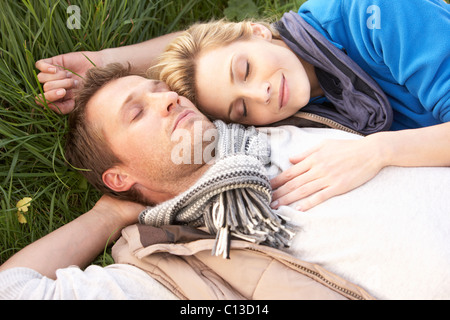 Young couple lying together on grass - Stockfoto