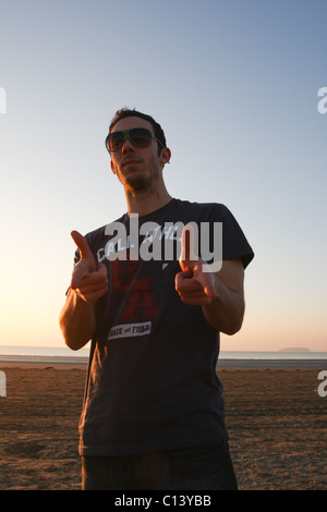 Young, fashionable man on beach wearing sunglasses as the sunsets - Stock Photo