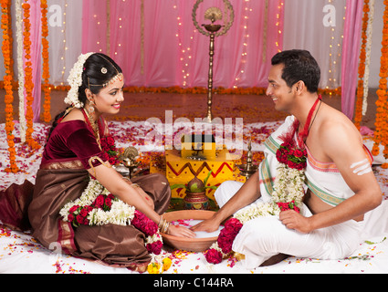 Newlywed couple playing Kangana Jua during South Indian wedding ceremony - Stock Photo