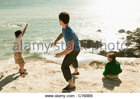 young girl throwing stone into sea on anglesey in wales. Black Bedroom Furniture Sets. Home Design Ideas