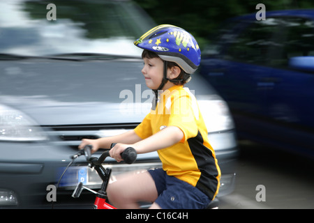 Five-year-old boy wearing a bicycle helmet riding a bike - Stock Photo