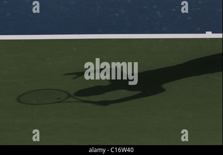 Shadow of a tennis player in action - Stock Photo