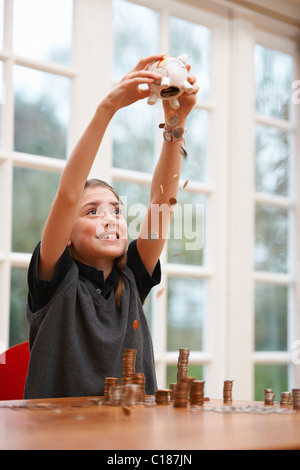 Girl emptying her piggy bank of coins - Stock Photo