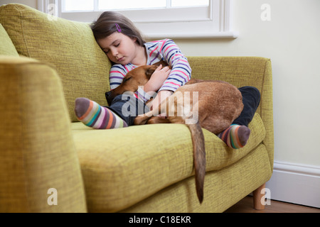 Young girl sleeping with her dog - Stock Photo
