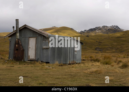 Deserted corrugated iron hut in a hilly landscape, Nevis Crossing, Cromwell, Otago, South Island, New Zealand - Stock Photo