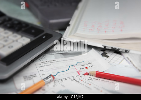 broken pencil tip on bear stock market sheet; calculator and paper pad can also be seen - Stock Photo