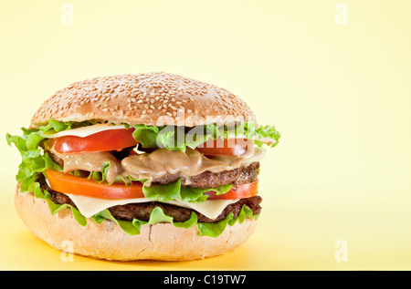 Tasty hamburger on yellow background. - Stock Photo