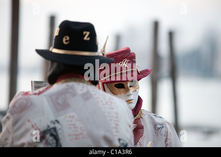 A couple in masks and costume pose by the Grand Canal, the Venice carnival, Venice, Italy - Stock Photo