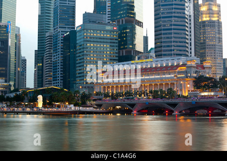 The Fullerton Hotel and finance district skyline at dusk.  Marina Bay, Singapore - Stock Photo