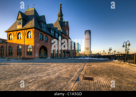 Central New Jersey Railroad station with the Goldman Sachs tower in the background at sunset - Stock Photo