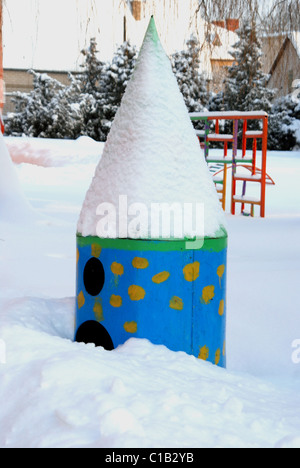 empty playground near kindergaten covered by snow in cold winter - Stock Photo