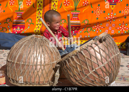 Young boy playing religious drums at a festival (Abbot's Birthday) at Phayang Gompa, (Ladakh) Jammu & Kashmir, India - Stock Photo