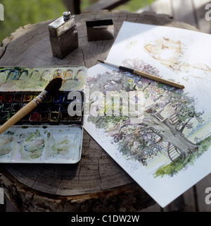 Watercolour palette and paintings on a tree stump - Stock Photo