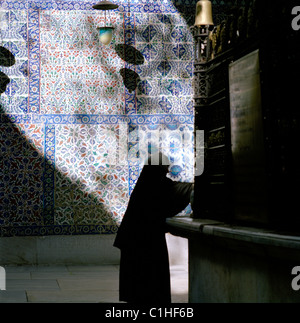 A Muslim woman outside the Iznik tiled tomb of Eyup Ensari at Eyup Sultan Mosque in Eyup in Istanbul in Turkey. - Stock Photo