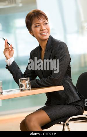 Portrait of African businesswoman sitting at the table during conference and looking aside - Stock Photo