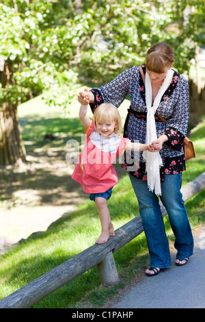 Mother assisting daughter walking on railing at zoo - Stock Photo