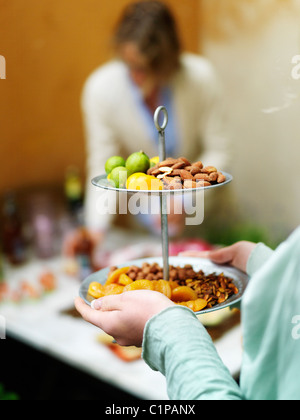 Close up of woman serving fruits and nuts - Stock Photo