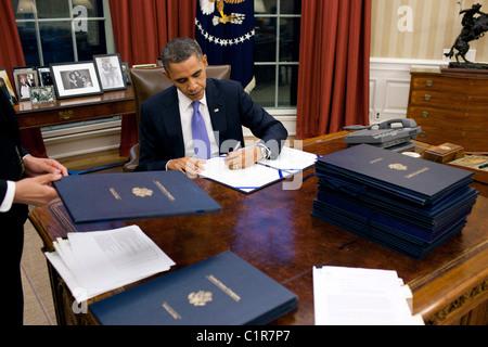 President Barack Obama signs legislation in the Oval Office, Dec. 22, 2010. - Stock Photo