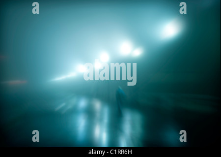 Mysterious figure walking on a wet foggy night. - Stock Photo