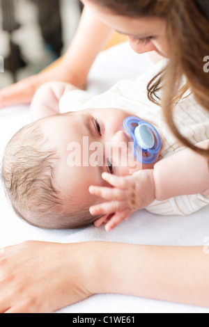 Close-up of a baby lying on a changing table while his mother is changing his nappy - Stockfoto