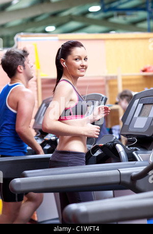 Athletic woman listening to the music while using a treadmill in a sport centre - Stockfoto