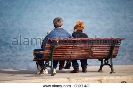 Couple sitting on a bench talking - Stock Photo