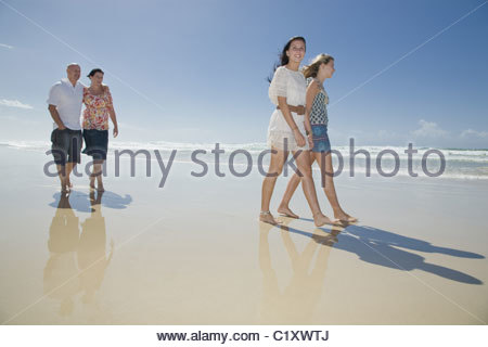 family walking on beach holding hands - Stock Photo