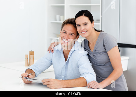 Portrait of a couple doing crossword together in the kitchen - Stock Photo