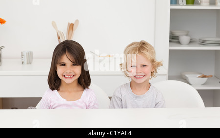 Lovely brother and sister sitting at a table in the kitchen - Stock Photo