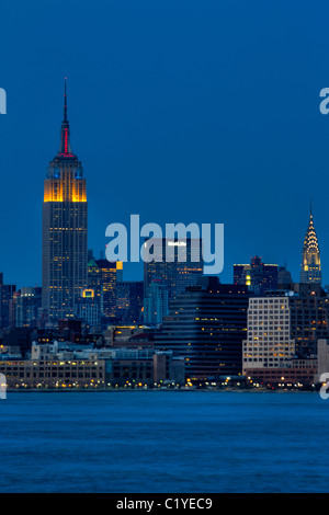 Empire State and Chrysler Buildings at night seen from New Jersey - Stock Photo