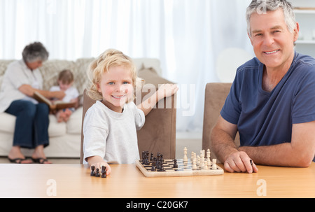 Young boy playing chess with his grandfather - Stock Photo