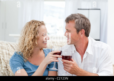 Couple drinking some red wine in the living room - Stockfoto