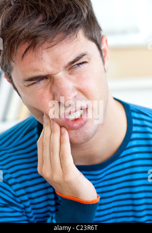 Unhappy man having a toothache in the living-room - Stock Photo