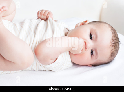 Portrait of a cute newborn baby lying on the sofa in his bedroom - Stockfoto
