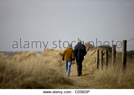 A senior couple walking along a path together, rear view - Stock Photo