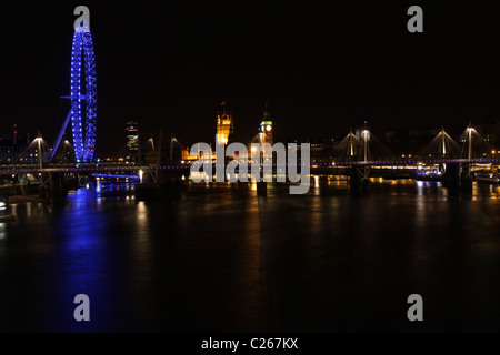 London Eye, Hungerford Bridge and Houses of Parliament reflected in River Thames at night London England  April - Stock Photo