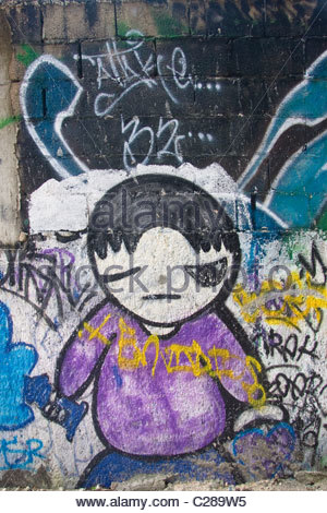 Graffiti art on a retaining wall in Cancun Mexico, of a winking boy in a purple shirt and blue pants. - Stockfoto