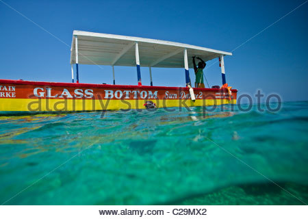 A person swims next to a glass bottom boat. - Stock Photo