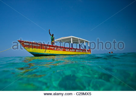 A guide waves from his glass bottom boat. - Stock Photo