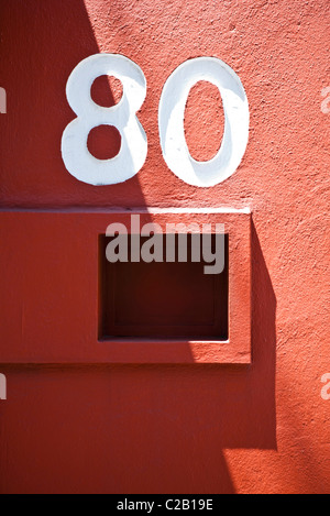 House number and mailbox on red wall - Stock Photo