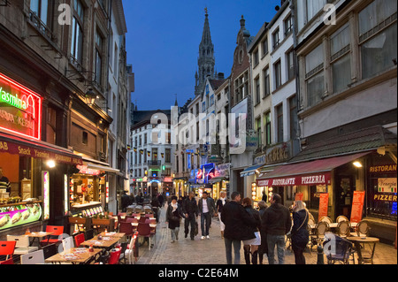 Bars and restaurants at night on the Rue du Marche aux fromages with the spire of the Hotel de Ville behind, Brussels, - Stock Photo