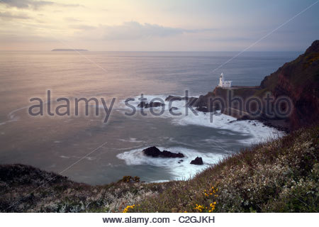 Lighthouse at Hartland Point and Lundy Island on the horizon, North Devon, England, UK - Stock Photo