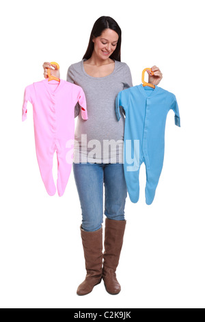 Photo of an attractive brunette woman who is 32 weeks pregnant holding a pink and blue baby grow,isolated on a white - Stock Photo