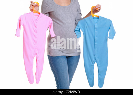 Photo of an attractive brunette woman who is 32 weeks pregnant holding a pink and blue baby grow - Stock Photo