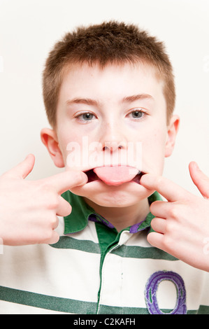 A MODEL RELEASED picture of an eleven year old boy pulling a funny face indoors - Stock Photo