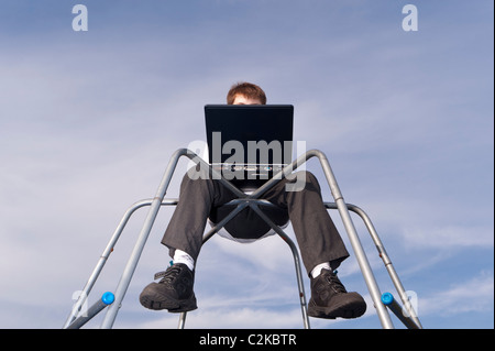 A MODEL RELEASED picture of an eleven year old boy using his laptop computer outdoors on a climbing frame in the - Stock Photo