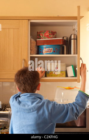 A MODEL RELEASED picture of an eleven year old boy looking in the kitchen cupboard to find food - Stock Photo