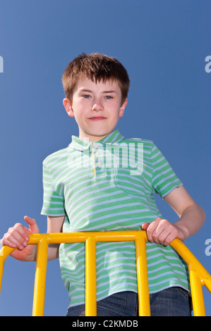 A MODEL RELEASED picture of an eleven year old boy outdoors on a climbing frame in the Uk - Stock Photo