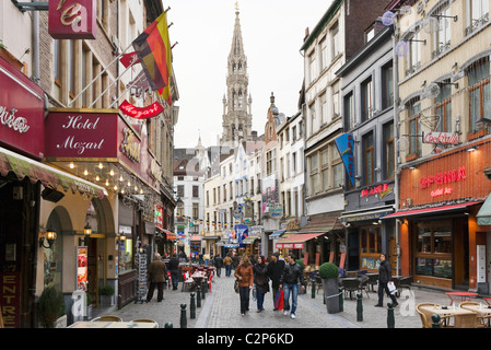 Bars and restaurants on the Rue du Marche aux fromages with the spire of the Hotel de Ville behind, Brussels, Belgium - Stock Photo