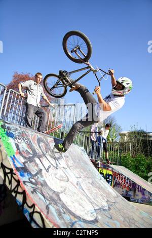 BMX biker performing tricks on a ramp - Stock Photo